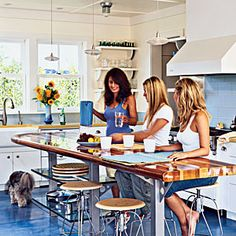 A longboard surfboard gets a second lift as a kitchen island table top in this environmentally friendly kitchen. EVERYTHING looks better w/pretty women in it. Love the surf board too.