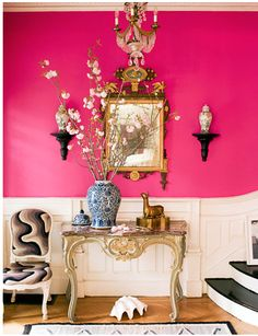 Am loving the bright pink wall with the pale pink paneling as well as the small shelving units. The gold/bronze-ish table looks good as well.