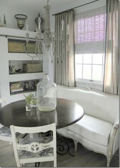 Kitchen nook with French sette, round table and built-in shelves all in white, greige, gray. by Tyrone