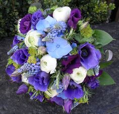 Bridal bouquet of purple anemones, muscari (grape hyacinths), blue hydrangea, purple lisianthus and white ranunculus from www.orchard-designs.co.uk