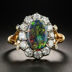Superbly hand-fabricated in silver over 18K rose gold around the turn-of-the-last-century (most likely of British origin), this fabulous halo ring features a modestly proportioned but remarkable gemstone. From the famed Lightening Ridge mines of Australia, this truly gemmy black opal exhibits an unparalleled play of colors (impossible to capture in still photos). Every imaginable hue (and then some!) combine to create a psychedelic, kaleidoscopic light show on your finger