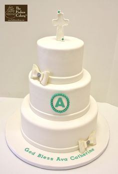 white communion cake with bows and monogram