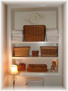 immaculate white painted over toilet storage with 3 tier open shelves for towel and rattan box place in small space tiny bathroom decoration designs