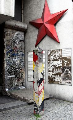 Boundary marker and piece of the Berlin Wall at the entrance of the Checkpoint Charlie Museum (Berlin).