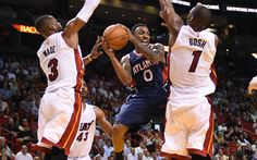 Atlanta's Jeff Teague looks to pass as the Heat's Dwyane Wade and Chris Bosh defend.