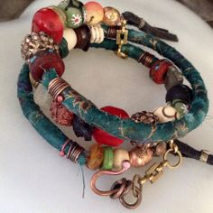 A tribal gypsy multi layered bracelet of memory wire sheathed in green and gold sari silk and an eclectic collection of boho beads including: - Red coral, etched bone,  - Ethiopian prayer, - African krobo, cast brass and recycled recycled glass Wraps around the wrist three times. As the beads are pretty heavy I've added a brass chain and copper hook so the wraps stay together on the wrist.