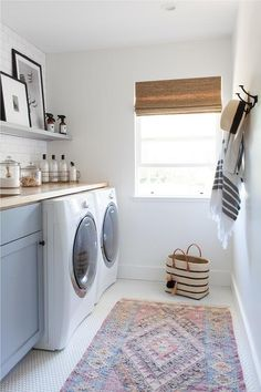 Laundry room designed with light blue cabinets, white hexagon floors, and a pink and blue vintage rug.