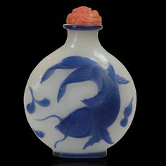 Beautiful opaque white glass snuff bottle with a dark blue glass overlay finely carved with a fan tailed carp design supporting a carved red glass stopper Chinese circa 1780-1850