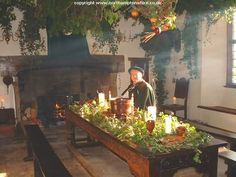 A man in Tudor clothes sitting in a room filled with greenery, a tradition that dates back to pre-Christian times.