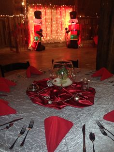 """Red and silver table scape with """"selfie"""" photo booth backdrop in the background at EPIC."""