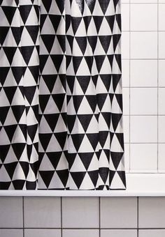 Graphic and monotonous expression in the bathroom with a shower curtain with triangles.