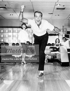1960s 1950s SMILING MAN SHOWING GOOD FORM IN BOWLING ALLEY
