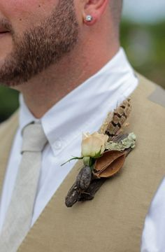 Woodsy boutonniere featuring bark, pods, pheasant feather and a rose.