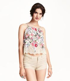 Short top in crinkled woven fabric with a printed floral pattern. Narrow cut at top with narrow shoulder straps, opening at back of neck with button, and lace trim at hem. Unlined.