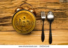 Alarm clock with fork and spoon - stock photo