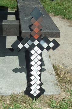 Minecraft sword made out of MDF then painted.  Cut this out of wood and painted it ready to hit the pinata with. An Enderman pinata with a cardboard box so it is pretty sturdy and could put up with the sword for long enough for everyone to have a turn.
