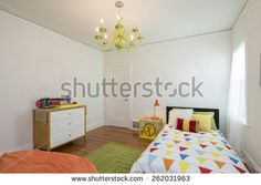 Children bedroom / kids room with light colorful decoration, green rug, bed, chandelier and modern chest. - stock photo