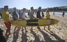 The Los Angeles Dodgers' Mike Baxter, second left, Tim Federowicz, third left, Drew Butera, third right, and Chris Withrow, help surf lifesavers Sophie Thomson and Dan Jewiss carry a rescue board down to the surf at Bondi Beach in Sydney, Wednesday, March 19, 2014. The Major League Baseball season-opening two-game series between the Los Angeles Dodgers and Arizona Diamondbacks in Sydney will be played this weekend. (AP Photo/Rick Rycroft)