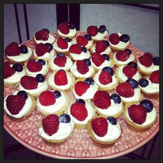 Delicious treats!  Shortbread cups filled with whipped cream and topped with a blueberry and raspberry. Sweet and yummy.