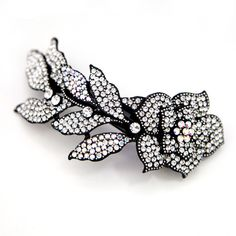 A large barrette with a black-casted metal body intricately designed with fine Swarovski crystals.  Perfect for a romantic updo for any formal occasion!