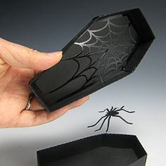 Spider web die cut from black vinyl gives a shimmering effect on matte paper coffin box. Attach fishing line to a spider for an extra BOO! Great invitation idea