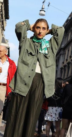 Jenny Walton in an oversized green army jacket with a green and white neck scarf