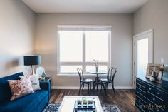 Andrea Beecher of cityhomeCOLLECTIVE design.  blue, gray walls, hardwood floors, living room, thonet chairs, black chairs