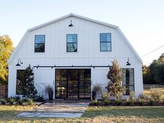 Large windows and traditional barn doors add a dramatic flourish to the new entrance for the beautifully remodeled ground floor. The outside stairs and upper porch were removed and an impressive set of doors added to replace the metal garage door that was there previously.