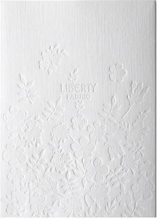 White on White impressed flower graphics and logo - Liberty Fabric