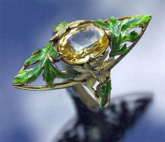 ART NOUVEAU  Chrysanthemum Ring   Gold Enamel Yellow Sapphire Diamond  H: 3.2 cm (1.26 in)   W: 1.4 cm (0.55 in)   Marks: Eagle's head  indistinct signature  French, c.1900  Yellow sapphire: 0.10 cm x 0.8cm, 3.15 cts approx.  A beautiful Museum quality enamelled Chrysanthemum ring set with a champagne coloured sapphire.  (Ref: 6591)