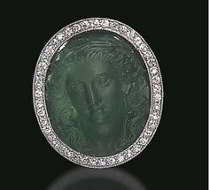 A BELLE EPOQUE EMERALD CAMEO AND DIAMOND RING   Set with a carved and frosted emerald cameo depicting a maiden in high relief, within a single-cut diamond surround, to the scrolling openwork gallery, mounted in gold, circa 1910