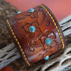 Hand made Herman Oak leather cuff with 8 Turquoise stones. I cut the leather layout the design and hand stamp/tool the pattern. The leather is