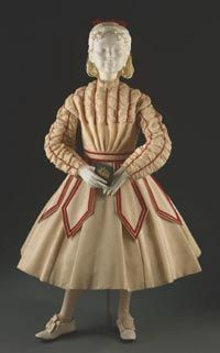 Girl's Dress    Made in United States  c. 1867-68    Artist/maker unknown, American. Worn by Mrs. J. Bertram Lippincott (Joanna Wharton).    Ivory wool plain weave, red silk velvet ribbon, cotton lace edging  Center Back Length (Dress): 30 1/2 inches (77.5 cm) Waist: 22 inches (55.9 cm)