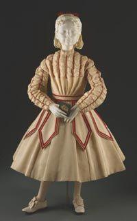 Girl's Dress    Made in United States  c. 1867-68    Artist/maker unknown, American. Worn by Mrs. J. Bertram Lippincott (Joanna Wharton).    Ivory wool plain weave, red silk velvet ribbon, cotton lace edging  Center Back Length (Dress): 30 1/2 inches (77.5 cm) Waist: 22 inches (55.9 cm)