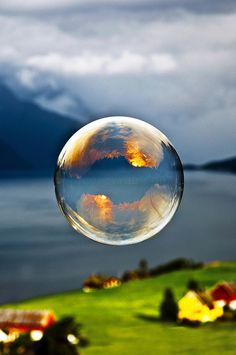Morning light reflected in a soap bubble over the fjord. シャボン玉,