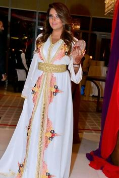 White kaftan with pink, orange, and red designs down the front. Gold belt. Igen garb.