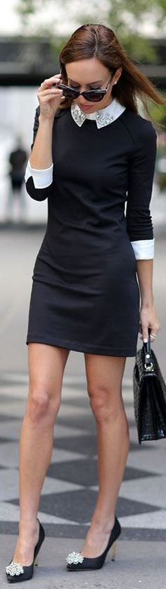 Black sheath dress with white embellished collar and white cuffs, black heels, and black handbag