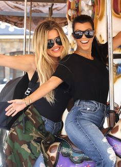 Khloe & Kourtney Kardashian rock smiles and trendy oversized shades while enjoying themselves on a carousel in Encino.