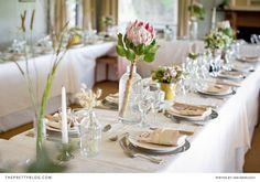 Great centrepiece idea with a Protea!  Full shoot on theprettyblog.com Photographer: Niki M Photography | Venue: Camp Figtree | Wedding Coordinator, Flowers, Decor, Cake: Marijke Niven