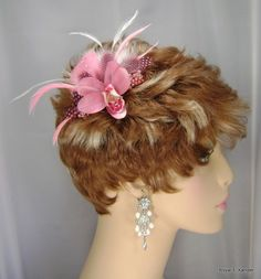 This hair fascinator can be worn by itself or with any bridal veil. The bride can wear it with her veil for the wedding ceremony, then remove the veil and wear the fascinator on its own for the reception. It is attached to a metal comb for easy positioning. <br />   <br />   Description:<br />   - Condition: Brand new - boxed with tags<br />   - Material: Feathers, Swarovski Crystals, Biots, beads, Pink Silk Orchid<br />   - Color: Pink&l...
