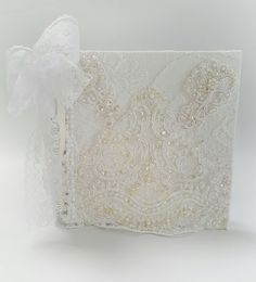 ************* This is an original design created by chiclaceandpearls************  This elegant Scrapbook Album features a white hardback album which i have covered in a lovely white linen fabric and a lace fabric over the top of that.I have also adorned the front of this beautiful album with gorgeous wedding appliques.I have put a lovely piece of white lace on the inside of the front and back.A beautful white lace bow and vintage style pearls drape from the side. Look after your memories…