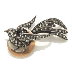 A diamond bird on moon brooch  composed of pavé-set rose-cut diamonds; mounted on silver-topped fourteen karat gold; length: 2 1/4in. Victorian or Victorian style.