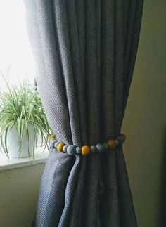 Finish off your windows in style with a set of curtain hold backs. Each hold-back consists of 15 x 3cm felt ball and 16 x 2cm felt balls and are available in a choice of 3 colour options. Each end has a loop and loose thread so you have an option of how to fix them. The one shown has been held back by putting the loop over the end ball of the other end. You can also tie the loose ends into a loop and hang on a wall hook or tie them back. Each tie back is approximately 80cm long and…