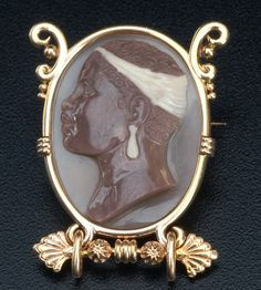 """Egyptian Revival agate cameo """"negress"""" brooch in 18k pink gold, 19th C. Unmarked. 19.9 gs. TW; 1 5/8"""" x 1 1/4""""."""