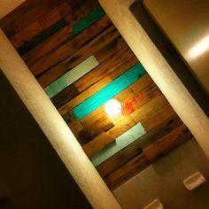 Proyecto #2 Tapiz en una de las paredes del baño, realizado con trozos de madera reciclada.