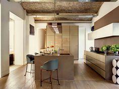 cocina moderna, vivienda rehabilitada, muebles color tierra sin tiradores, isla central con fregadero y zona de barra, suelo de parquet