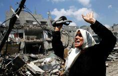 A Palestinian woman cries as she flees from the Al Shejaeiya neighbourhood, during an Israeli military operation in the east Gaza City, 20 J...