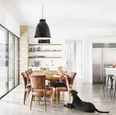 Dining Room With Black Pendant Lights And Leather Chairs