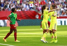 Claudine Meffometou #12 of Cameroon looks on as Yuika Sugasawa #15 and Yuki Ogimi of #17 Japan celebrate Japan's first goal during the FIFA Women's World Cup Canada 2015 Group C match between Japan and Cameroon June 12, 2015 at BC Place Stadium in Vancouver, British Columbia, Canada. (Photo by Jeff Vinnick/Getty Images)