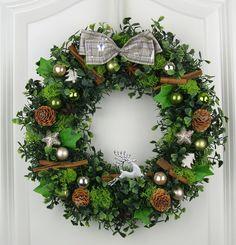 Dekorativer Türkranz für die Weihnachtszeit. Dieser Weihnachtskranz ist verziert mit Kunst- und Naturprodukten wie Weihnachtskugeln in grün und silber / gold Tönen, weißen Tannenbäumen, glitzernen Sternen, Zimtstangen, Sternanis, Zapfen, künstlicher Tanne, Buchs, Efeu und Moos auf einem Strohkranz. In Handarbeit angefertigt.